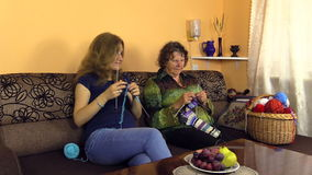 Grandma with girl knit needles on couch, experience, hobby craft stock video