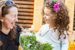 Grandma gives granddaughter bouquet of flowers stock images