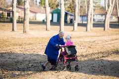 Grandma giving granddaughter a ride on her walker Stock Images