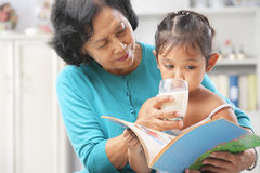 Grandma giving milk to her granddaugter Stock Photography