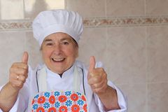 Grandma giving thumbs up in the kitchen.  stock image