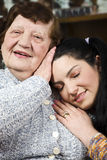 Grandma and grandaughter loving. Granddaughter sitting with eyes closed on her grandmother chest and the grandma holding her hand on girl head,check also Royalty Free Stock Photos