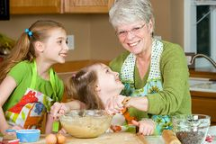 Grandma and Grandchildren in the kitchen. A Grandmother baking cookies with two kids in the kitchen royalty free stock photo