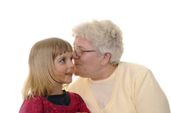 Grandma and granddaughter. Grizzled grandma and blond granddaughter whispering Royalty Free Stock Images