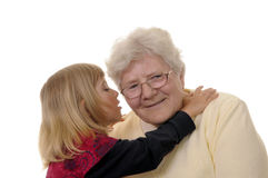 Grandma and granddaughter. Grizzled grandma and blond granddaughter whispering Royalty Free Stock Photography