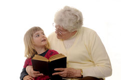 Grandma and granddaughter. White-haired grandma read to granddaughter royalty free stock photos