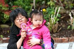 Grandma and Granddaughter. Grandma blowing bubbles for her first granddaughter Royalty Free Stock Images