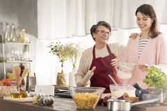 Grandma and granddaughter baking a cake stock image