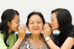Grandma and granddaughter closeness. Two granddaughter whispering some news to their old grandmother Stock Image