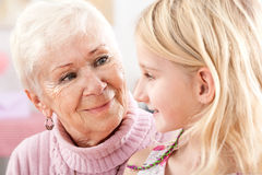 Grandma and granddaughter closeup. A closeup of a grandma and a granddaughter looking at each other Royalty Free Stock Images