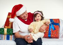 Grandma and granddaughter dressed in santa hat with gift boxes sit on sofa, white background. New year eve and christmas holiday c Royalty Free Stock Images