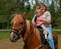 Grandma and Granddaughter Horse Riding. This Caucasian grandma has her toddler 2 year old granddaughter with her riding a Peruvian Passo horse in this country Royalty Free Stock Photography