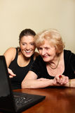 Grandma and granddaughter with a laptop. A picture of a granddaughter showing something on the laptop to her grandma Royalty Free Stock Photos