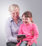 Grandma and granddaughter looking at the gadget Stock Photo