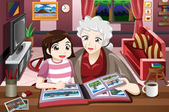 Grandma and granddaughter looking at picture album Stock Images