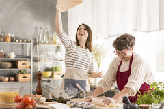 Grandma and granddaughter making pizza. Happy grandma and granddaughter making pizza in modern kitchen royalty free stock photos