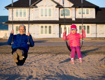 Grandma and granddaughter swinging at a playground Stock Photos