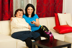 Grandma and granddaughter wath tv. Grandma and adult granddaughter watch tv together in living room Royalty Free Stock Photo