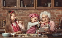 Grandma with granddaughters looking for a recipe in tablet. Grandma with her little granddaughters looking for a recipe using modern tablet Stock Images