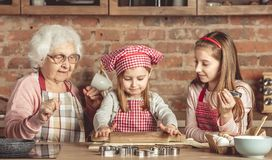 Grandma and granddaughters spreading dough royalty free stock photography