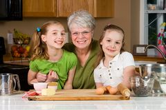 Grandma and Grandkids. A gray haired Grandmother baking cookies with her Grandchildren Royalty Free Stock Images