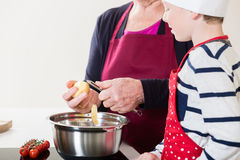Grandma and grandson cooking together. In domestic kitchen stock photos