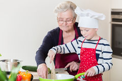 Grandma and grandson cooking together. In domestic kitchen royalty free stock photos