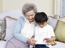 Grandma and grandson. Looking at tablet computer together Royalty Free Stock Images