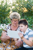 Grandma with  grandson watching tablet PC Stock Image