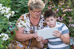 Grandma with  grandson watching tablet PC Stock Photos