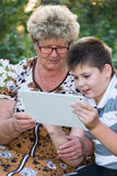 Grandma with  grandson watching tablet PC Royalty Free Stock Image