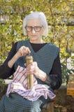 Grandma grinding coffee on a vintage coffee grinder Royalty Free Stock Images