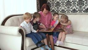 Grandma and her grandchildren look wedding album. Grandmother and her four grandchildren look wedding album sitting on the sofa stock video
