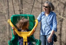 Grandmother and granddaughter play in plastic swing Royalty Free Stock Photography