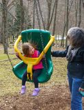 Grandmother and granddaughter play in plastic swing Stock Photos