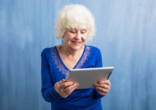 Grandma holding tablet computer Stock Images