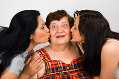Grandma kissed by two granddaughters. Surprised grandma is kissed by her granddaughter on cheeks,check also  Grandmother Royalty Free Stock Photo