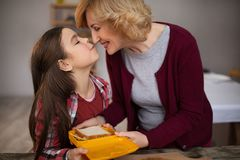 Beautiful grandma and granddaughter are making sandwiches. Grandma kissing her granddaughter and giving luch box with sandwich Stock Photography