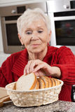Grandma at kitchen. Elder disabled woman preparing breakfast herself stock photo