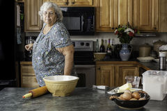 Grandma in a kitchen preparing to bake. A grandmother or mother in a kitchen looking at supplies getting ready to bake royalty free stock photos