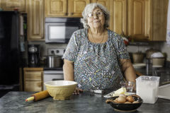 Grandma in a kitchen preparing to bake Stock Photos