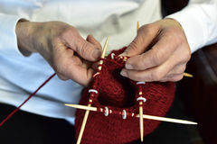 Grandma knitting a hat. Grandmas hands knitting a hat with double pointed bamboo needles Royalty Free Stock Photo
