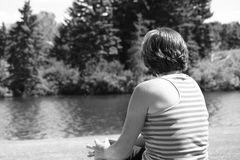 Grandma. Lady sitting on a bench at the park watching the water Stock Photos