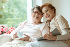 Grandma laughing with her granddaughter. Happy grandma with glasses holding cup of coffee and laughing with her granddaughter volunteering as caretaker stock image