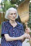 Grandma leaning on a broom and resting from housework Stock Images