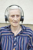 Grandma listening to music with headphones Stock Image