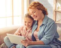 Grandma and little girl at home. Cute little girl and her beautiful grandma are using a digital tablet, hugging and smiling while sitting on couch at home Royalty Free Stock Photo