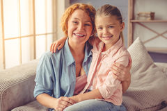 Grandma and little girl at home. Portrait of cute little girl and her beautiful grandma hugging, looking at camera and smiling while sitting on couch at home Stock Photography