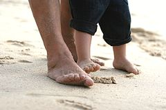 Grandma and the little one's feet in the sand Royalty Free Stock Photos