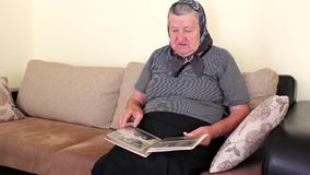 Sad Grandma Looking Photo Album with Old Pictures stock video